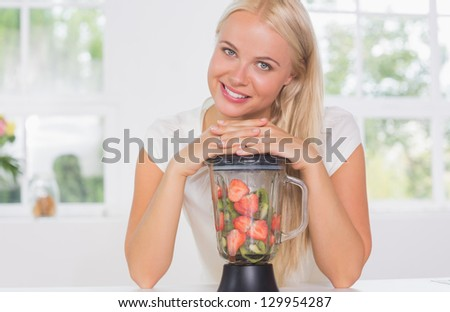 Smiling woman putting hands on the mixer in the kitchen - stock photo