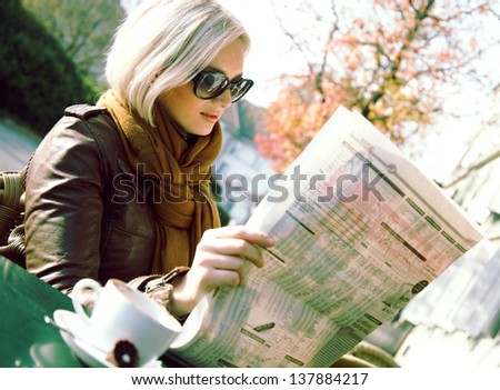 Smiling woman reading newspaper in the outdoor cafe - stock photo