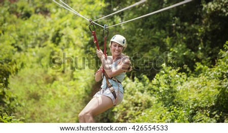 Smiling woman riding a zip line in a lush tropical forest  - stock photo