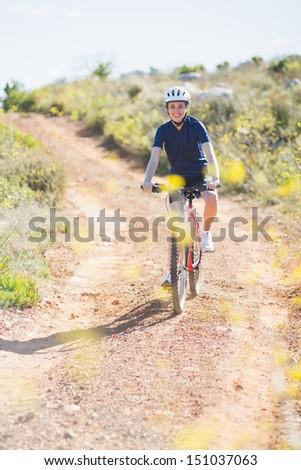Smiling woman riding bike and looking at camera - stock photo