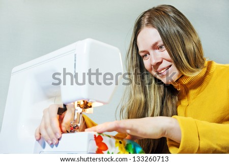 Smiling woman seamstress work on the sewing-machine - stock photo