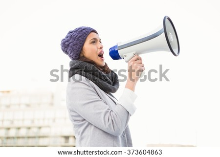 Smiling woman shouting with megaphone outdoor - stock photo