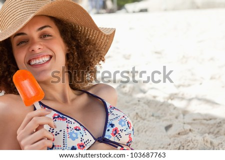 Smiling woman showing a beaming smile while holding a delicious orange popsicle - stock photo