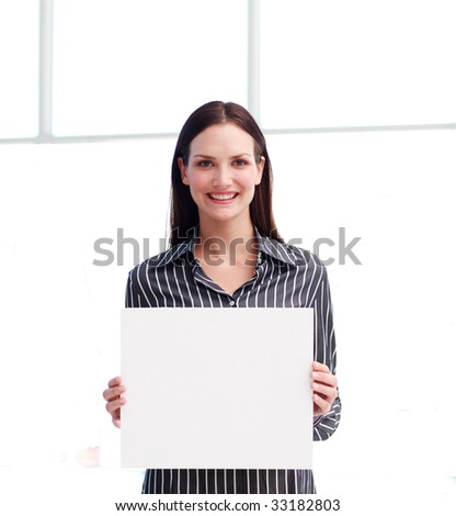 Smiling woman showing a big business card in office - stock photo
