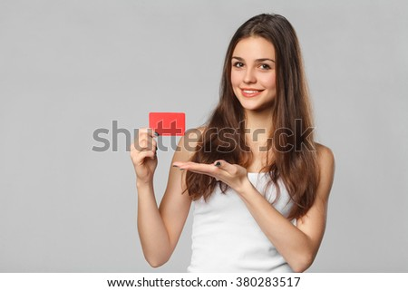 Smiling woman showing blank credit card in white t-shirt, isolated over gray background - stock photo