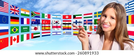 smiling woman shows international flags - stock photo