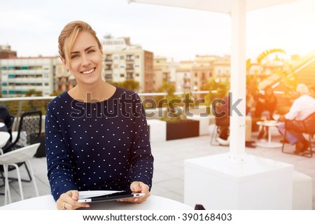 Smiling woman sits in modern coffee shop interior with touch pad and looks at camera during her free time, happy female student is using portable digital tablet during morning breakfast in restaurant  - stock photo