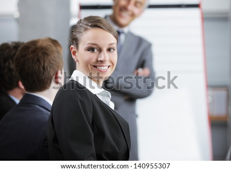 Smiling woman sitting at a business meeting with colleagues - stock photo