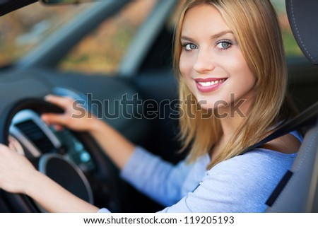 Smiling woman sitting in car - stock photo