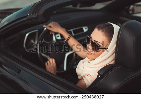 Smiling woman sitting in car, Happy girl driving automobile, outdoors summer portrait.  Young woman driving on road trip on beautiful sunny summer day.Portrait sexy fashion woman model in sunglasses - stock photo