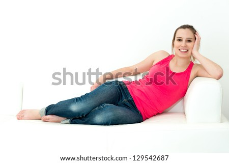 Smiling woman sitting on her sofa - stock photo