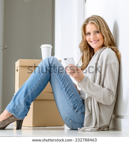 Smiling woman sitting on the floor with a pile of boxes, having a coffee break and texting with her smart phone - stock photo