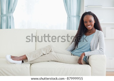 Smiling woman sitting with legs on her sofa - stock photo
