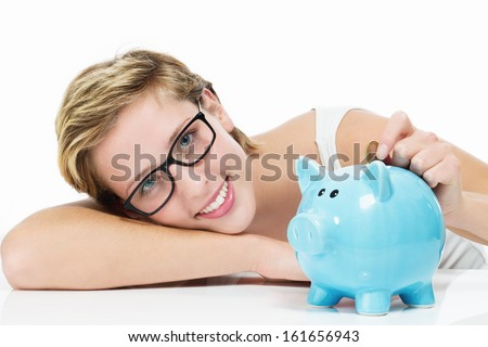 smiling woman throwing money in her piggy bank on white background - stock photo