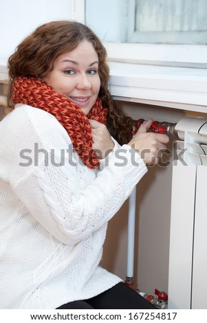 Smiling woman turning thermostat on central heating radiator - stock photo