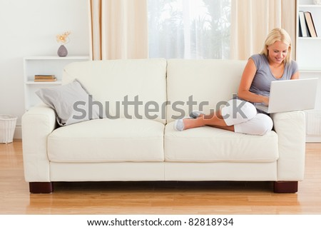 Smiling woman using a notebook in her living room - stock photo
