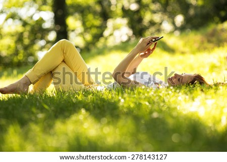 Smiling woman  using a smart phone and relaxing at the park on grass. - stock photo
