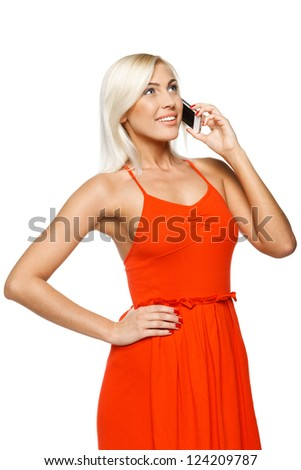 Smiling woman using cell phone looking up over white background - stock photo