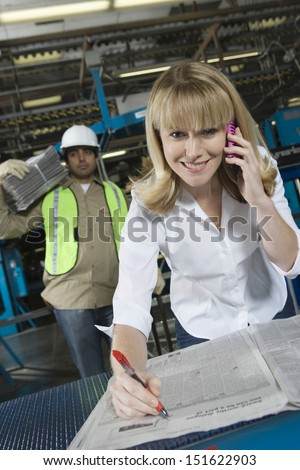 Smiling woman using cellphone while checking newspaper in the factory - stock photo