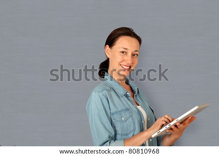 Smiling woman using electronic tablet - stock photo