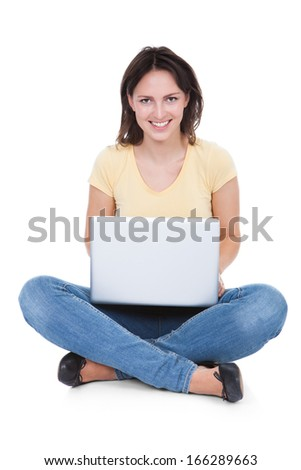 Smiling Woman Using Laptop Sitting On White Background - stock photo