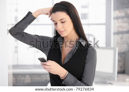 Smiling woman using mobile phone for texting, standing in office, thinking.? - stock photo