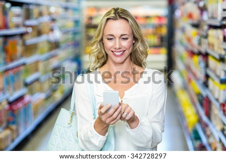 Smiling woman using smartphone in supermarket - stock photo