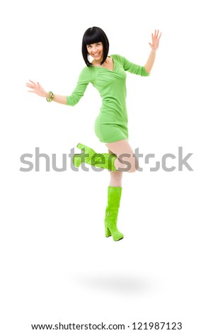 smiling woman wearing a green dress and green shoes jumping on a isolated white background - stock photo
