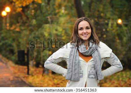 Smiling woman wearing knitted jacket in autumn evening park. - stock photo