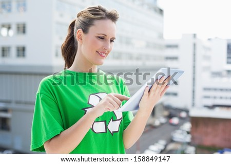 Smiling woman wearing recycling tshirt using tablet outside - stock photo