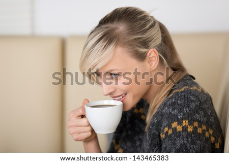 Smiling woman with a freshly brewed cup of espresso coffee in her hand sitting on a comfortable couch, head and shoulders side view portrait - stock photo