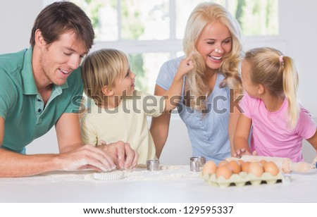 Smiling woman with a rolling pin in hands in kitchen - stock photo