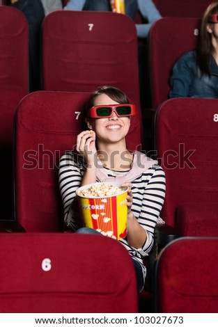 Smiling woman with a snack in the 3D movie - stock photo