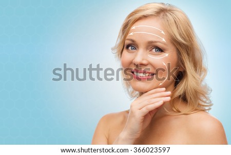 smiling woman with bare shoulders touching face - stock photo