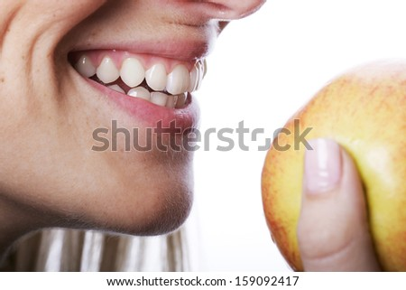 Smiling woman with beautiful teeth about to bite into a ripe juicy apple that she is holding in her hand, close up of her mouth isolated on white - stock photo