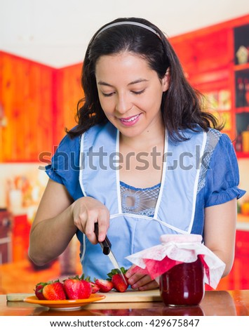 Smiling woman with blue apron preparing a recipe with strawberries - stock photo