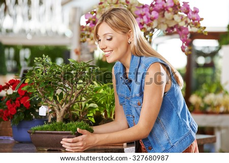 Smiling woman with bonsai apple tree in a nursery - stock photo