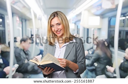 smiling woman with book on train - stock photo