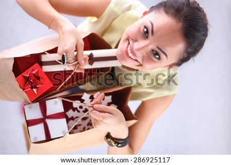 Smiling woman with christmas gifts . - stock photo