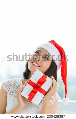 Smiling woman with Christmas present looking up - stock photo