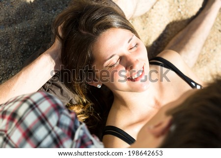 Smiling  woman with closed eyes lying on the lap of a  man on the beach - stock photo
