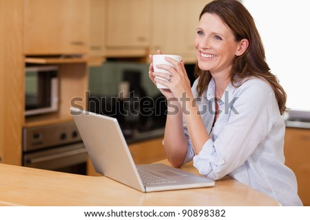 Smiling woman with cup and notebook in the kitchen - stock photo