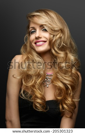Smiling woman with curly hair on a gray background - stock photo
