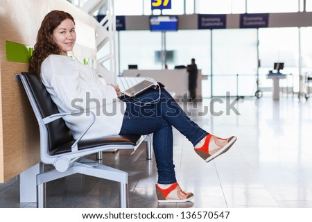 Smiling woman with devices sitting in airport lounge - stock photo