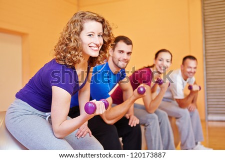 Smiling woman with dumbbells exercising in sports group in gym - stock photo