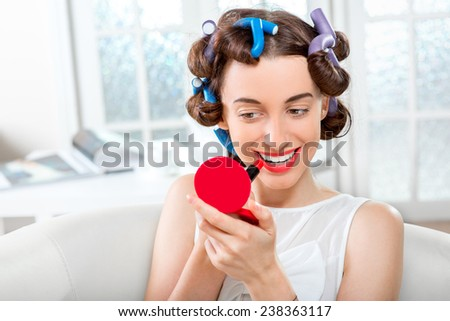 Smiling woman with hair curlers using lipstick on white domestic background - stock photo