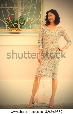 smiling woman with handbag near old house. instagram image filter retro style - stock photo