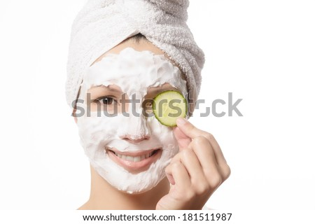 Smiling woman with her hair tied up in a white towel and a deep cleansing nourishing face mask applied to her skin holding a refreshing slice of cucumber to her eye in a beauty and skincare concept - stock photo