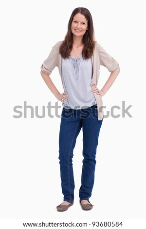 Smiling woman with her hands on her hip against a white background - stock photo