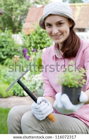 Smiling woman with herbs and hoe in garden - stock photo